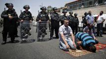 Policia de choque israelita em vigilância enquanto muçulmanos rezam em Jerusalém. Foto: Ahmad Gharabli