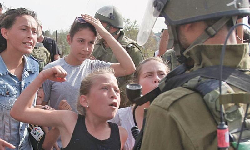 Foto: AFP 2012. Ahed Tamimi mostra o punho a um soldado israelita.