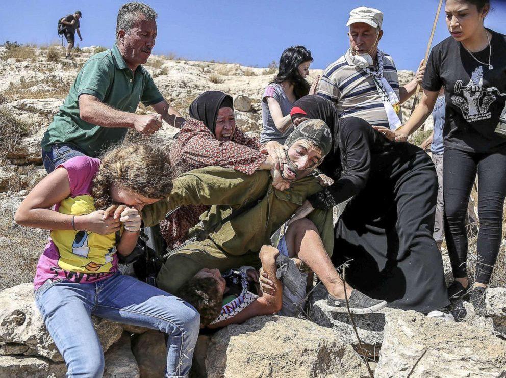 Foto: Issam Rimawi/Anadolu Agency/Getty Images  28 de Agosto de 2015. Ahed Tamimi reage à tentativa por parte de um soldado israelita de prender uma criança.